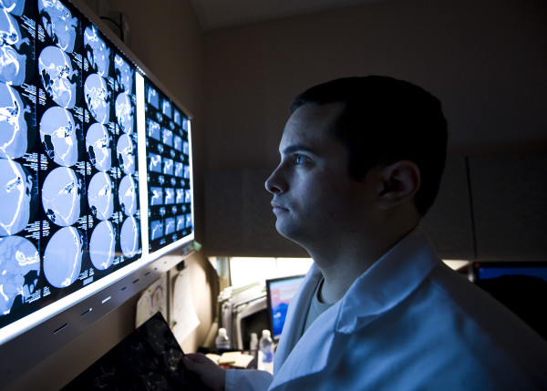 Capt. (Dr.) Wesley Reynolds studies a patient's computed tomography scan at the Mike O'Callaghan Federal Medical Center March 18, 2014, at Nellis Air Force Base, Nev. March is brain injury awareness month. According to the Brain Injury Association of America, about 75 percent of traumatic brain injuries are concussions or other forms of mild TBIs. Reynolds is a 99th Medical Operations Squadron neurologist. (U.S. Air Force photo/Senior Airman Jason Couillard)