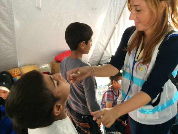 In 2014, EU aid workers give Syrian children in Iraq polio vaccinations per os.